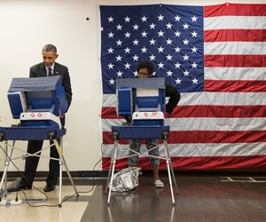 President Barack Obama, center, votes early in the midterm election at the Dr. Martin Luther King Community Service Center Monday, Oct. 20, 2014, in Chicago.