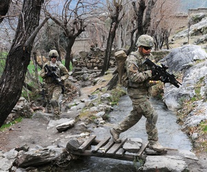 Two soldiers cross a stream during a unit visit to a village in Afghanistan's Kunar province.