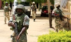 Nigerian soldiers stand guard at the offices of the state-run Nigerian Television Authority in Maiduguri, Nigeria.