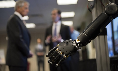 In the foreground, Defense Secretary Chuck Hagel learns about one of the prosthetics developed as part of DARPA's Revolutionizing Prosthetics program.