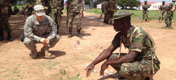 A California National Guard Special Forces Soldier Reviews A Sand Table Map With A Nigerian Soldier