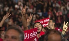 Supporters of Hamma Hammami, head of the Popular Front party, flash the victory sign during a campaign rally in Tunis, Sunday, Nov. 16, 2014.
