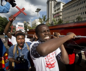 Protestors carry mock coffins and carry crosses during a protest following a recent attack on a bus by Somali militant group al-Shabab.