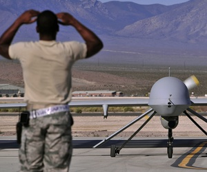 A crew chief marshals an MQ-1B Predator drone as it taxies in preparation for a training mission, on May 13, 2013.