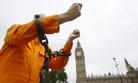 A protester holds up his chained arms during a protest against the Guantanamo Bay detention camp, in Parliament Square in London, Wednesday, Oct. 15, 2014.