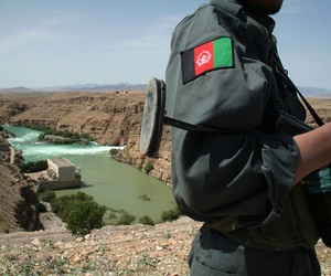 An Afghan police officer stands guard as the Kajaki power dam is seen in the background in Kajaki, Helmand province, south of Kabul, Afghanistan, April 16, 2008.