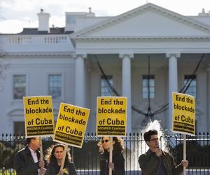 "People from the ANSWER Coalition hold signs urging the U.S. to ""End the blockade of Cuba,"" during a demonstration outside of the White House on Decmeber 17, 2014."