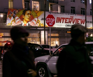 "People walk past a banner for ""The Interview""at Arclight Cinemas, Dec. 17, 2014, in the Hollywood section of Los Angeles."