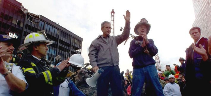 President George W. Bush stands with a firefighter on a burnt fire truck in front of the World Trade Center during a tour after 9/11, on September 14, 2001.