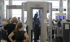 Passengers are scanned at a security checkpoint at Logan Airport, in Boston, on October 24, 2012.
