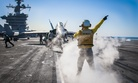 A Royal Navy Chief directs an F/A 18 Hornet onto a catapult on the flight deck of the USS Carl Vinson, on January 1, 2015.