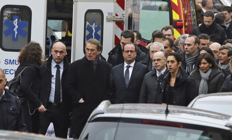 French President Francois Hollande, center, flanked with security forces gestures, as he arrives outside the French satirical newspaper Charlie Hebdo's office, in Paris, Wednesday, Jan 7th