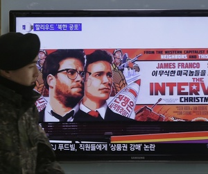 A South Korean army soldier walks near a screen showing the trailer of The Interview.