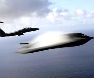 A B-2 Spirit and F-15 Strike Eagles fly in formation across the Pacific Ocean.
