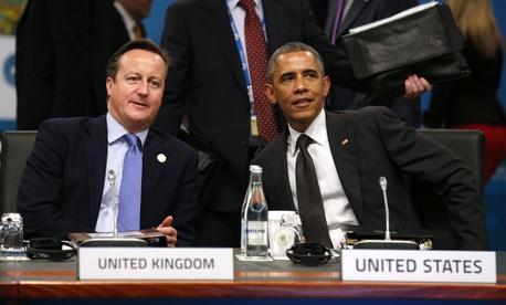 President Barack Obama and British Prime Minister David Cameron talk at the start of the plenary session at the G20 Summit in Brisbane, Australia, on November 15, 2014.