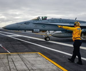 A sailor aboard the USS John C. Stennis direcs an F/A 18 during a training exercise, on December 10, 2014.