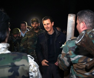 Syrian President Bashar Assad speaks with Syrian troops during his visit on the front line in Damascus district of Jobar, on December 31, 2014