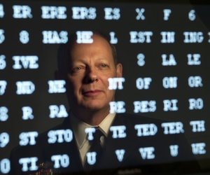 Navy Rear Admiral William E. Leigher, one of the nation's top military experts on cyber security, is reflected in a computer screen displaying a numerical code.