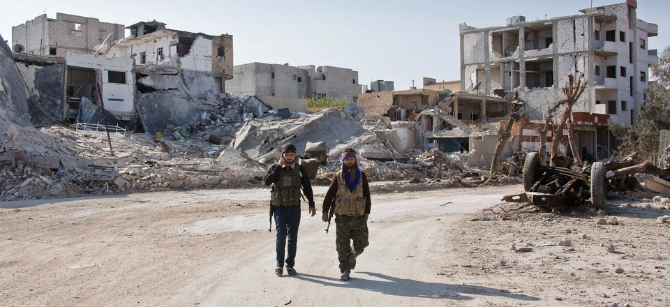 Kurdish People's Protection Units (YPG) soldiers walk near the town entrance circle heading to their strongholds in Kobani, Syria, on Nov. 19, 2014.