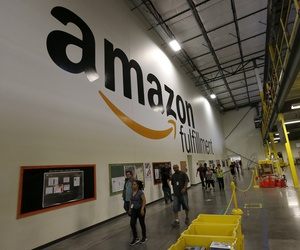 """Amazon.com employees go back to work after a short break at an Amazon.com Fulfillment Center on """"Cyber Monday"""" on the busiest online shopping day of the holiday season Monday, Dec. 2, 2013, in Phoenix."""