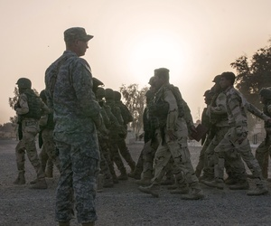 A soldier watches as Iraqi Army troops march on Camp Taji, on Feb. 13, 2015.