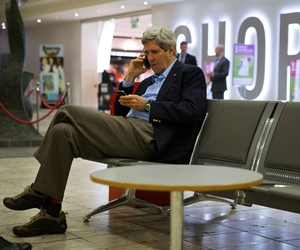 U.S. Secretary of State John Kerry speaks on his cell phone at Shannon Airport in Ireland, Saturday March 29, 2014, during a refueling stop.