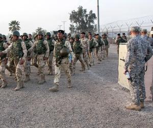 U.S. soldiers watch as Iraqi army soldiers march on Camp Taji, Iraq, Feb. 13, 2015.