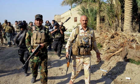 Iraqi security forces and Shiite militia men patrol Jurf al-Sakhar, 43 miles south of Baghdad, Iraq, on October 26, 2014.