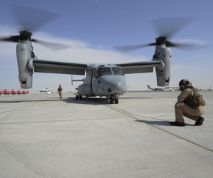 Two Marine sergeants perform a preflight check on an MV-22 Osprey prior to a flight at the 2013 Dubai Airshow.