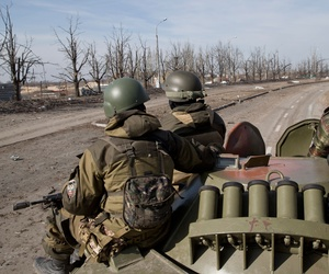 Russia-backed rebels sit on an armored transporter driving to the airport outside Donetsk, Ukraine, Wednesday, Feb. 25, 2015.
