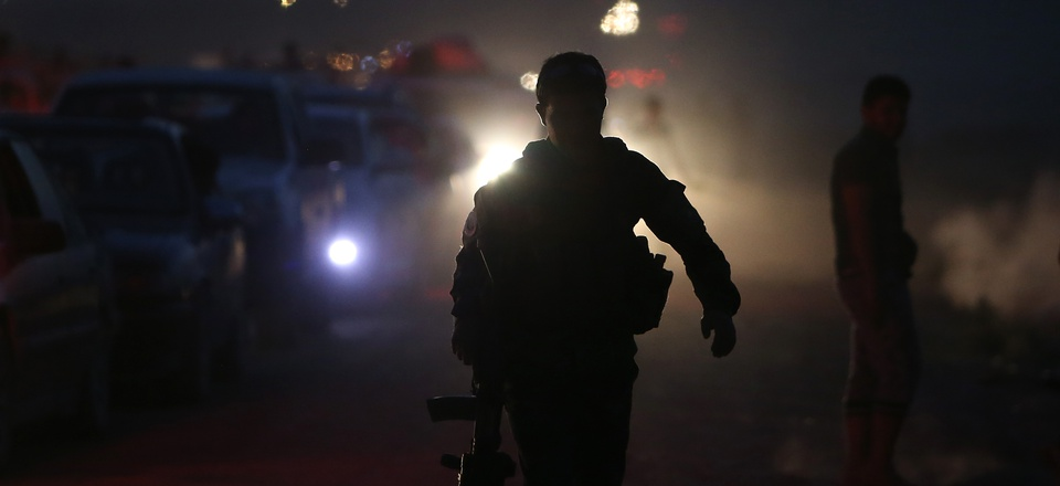 A Kurdish security soldier is seen silhouetted as he walks by along queue of cars carrying Iraqi citizen fleeing from Mosul and other northern Iraqi towns, in the Khazer area between the Iraqi city of Mosul and the Kurdish city of Irbil, northern Iraq.