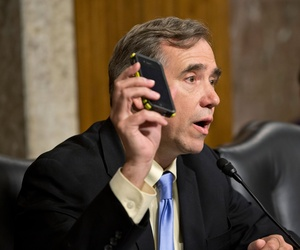 Senate Appropriations Committee member Sen. Jeff Merkley, D-Ore. holds up his Verizon cell phone during the committee's hearing on cybersecurity and funding, June 12, 2013, on Capitol Hill.