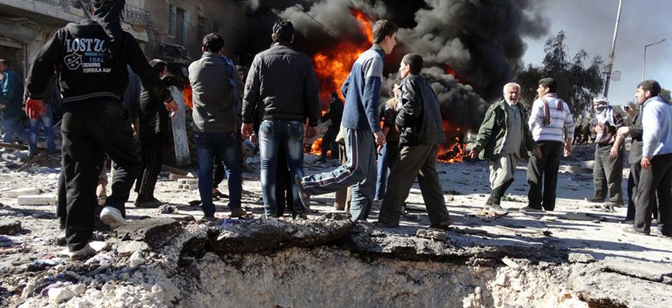 Syrian citizens gather near flames caused by a government forces warplane attack in al-Bab neighborhood of Aleppo, Syria, on Feb. 1, 2014.