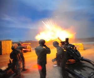 An M119A2 crew sends a round down range during a night training fire mission at Forward Operating Lightning, Afghanistan, on Nov. 11, 2013.