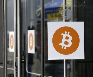 Bitcoin logos are displayed at the Inside Bitcoins conference and trade show, on April 7, 2014.