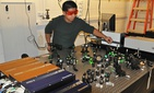 A graduate student performs sensitive measurement of interfacial thermal transport using an ultrafast laser system.