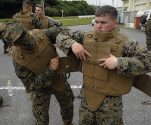 Marines with the 3rd Marine Logistics Group help each other configure their new Modular Tactical Vests before vest trainers inspect individual Marines for proper fit.