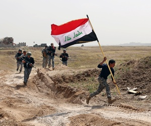 A member of the Iraqi security forces runs to plant the national flag as they surround Tikrit during clashes to regain the city from Islamic State militants.