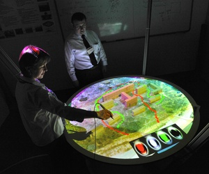 A research associate professor at the Naval Postgraduate School demonstrates the virtual sand table for urban warfare operations training rehearsals at Monterey, Calif., July 22, 2009.
