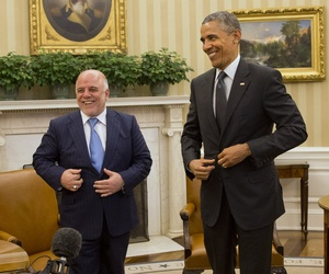 Iraqi Prime Minister Haider Al-Abadi and President Barack Obama fix their suit jackets as they finish their meeting in the Oval Office of the White House in Washington, Tuesday, April 14, 2015.