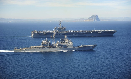 The Ticonderoga-class guided missile cruiser USS Vicksburg (CG 69) escorts the Nimitz-class aircraft carrier USS Theodore Roosevelt (CVN 71) as they pass the Rock of Gibraltar while transiting the Strait of Gibraltar.