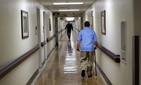 In this March 11, 2015 photo, a patient walks down a hallway at the Fayetteville Veterans Affairs Medical Center in Fayetteville, N.C.