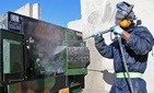 A private contractor sprays water to clean parts of a generator at Forward Operating Base Shank, Logar province, Afghanistan, March 14, 2012.