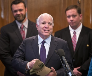 Senate Armed Services Committee Chairman Sen. John McCain, R-Ariz. holds a hat with an image of the A-10 aircraft and the word 'treason' given to him prior to a news conference on Capitol Hill in Washington,Tuesday, May 5, 2015.