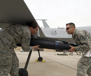 Two Air Force NCOs load munitions on an MQ-9 Predator.