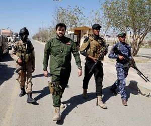 Members of Iraq's Sunni tribes walk at the front line during a battle with ISIS militants in Tikrit, Iraq, on March 16, 2015.
