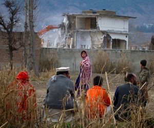 n this Feb. 26, 2012 file picture, a Pakistan family watches the destruction of Osama bin Laden's compound in Abbottabad, Pakistan.