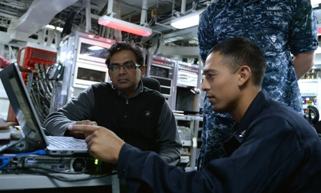 A member of Operation Trident Warrior shows sailors aboard the USS Peleliu how to use a Malicious Activity Security Tool.
