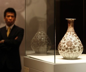 Pilfering data isn't like stealing this vase. A security man stands guard next to a early Ming underglaze copper-red vase during an auction by Christie's in Hong Kong Tuesday, May 30, 2006.