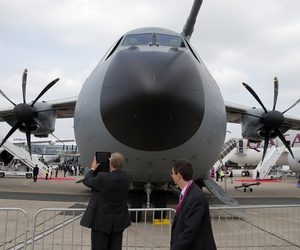 Visitors look at the Airbus A400M military transport aircraft presented at the Paris Air Show, at Le Bourget airport, north of Paris, Monday, June 15, 2015.